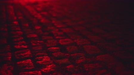 paving blocks : Wet illuminated by red light cobblestone paving street at night Stock Footage
