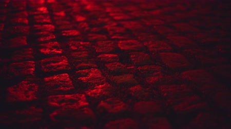 paving : Wet illuminated by red light cobblestone paving street at night Stock Footage