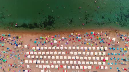 parasol : Aerial top view on the beach. Umbrellas, people, sand and sea waves Stock Footage