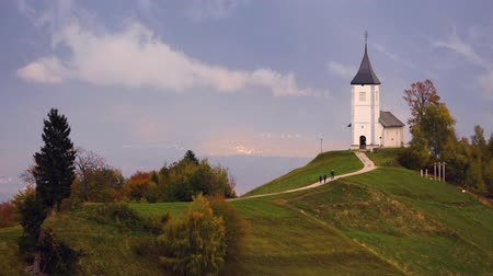 slovenya : Jamnik, Slovenia - Panoramic view over the church of St. Primoz in Slovenia near Jamnik with beautiful clouds and Julian Alps at background. Stok Video