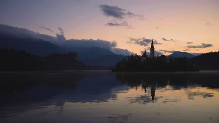 marys : Lake Bled, Slovenia with St. Marys Church of the Assumption on the island, sunset and dramatic clouds Stock Footage
