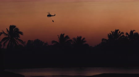 vigili : Rescue fire helicopter collects water into the sea and flies toward the extinguish a tropical forest fire on the background of a beautiful dawn sky. Jungle Fire Prevention