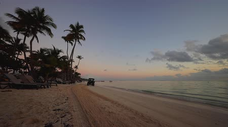 saona : Sunrise over tropical island beach in Punta Cana, Dominican Republic. Tractor cleaning the seand