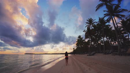 saona : Girl running on tropical beach early in the morning. Sunrise over caribbean island Dominican Republic Stock Footage