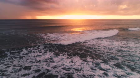 сумерки : Surfing ocean waves and dramatic sea sunrise, aerial view