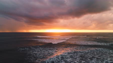 célállomás : Aerial view of burning sky and golden sunrise over ocean waves, caribbean sea Stock mozgókép