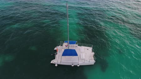 Канкун : Aerial view over Caribbean sea. Catamaran or sailboat in the water at sunrise Стоковые видеозаписи