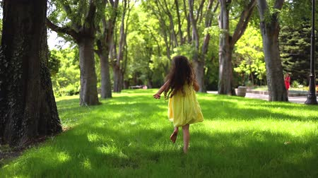 despreocupado : Happy little girl with yellow dress running barefoot on green grass in the park Stock Footage