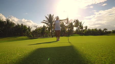 ゴルフ : Golf course and champion player near the hole with flag, luxury tropical resort 動画素材