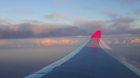 okno : Plane flying above clouds over the ocean and tropical islands. Morning sunrise with Wing of an airplane