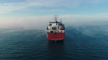 vinç : Aerial view of cargo container  ship sails in sea fog, crane vessel working for delivery of delivery containers.