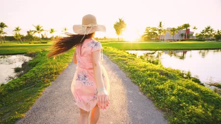dominican : Follow me concept of young woman running on tropical golf course path. Summer vacation or holiday Stock Footage