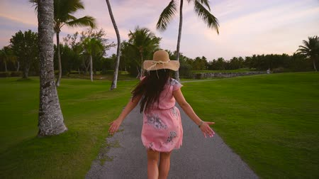 takip etmek : Follow me concept of young woman running on tropical golf course path. Summer vacation or holiday Stok Video