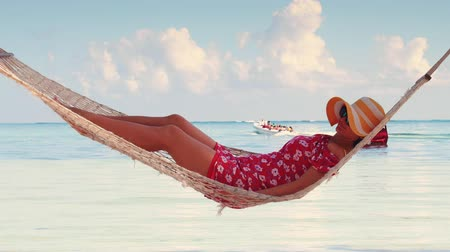 купальник : Girl relaxing in a hammock on tropical island beach. Summer vacation in Punta Cana, Dominican Republic Стоковые видеозаписи