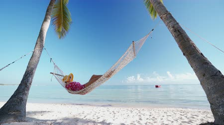 Girl relaxing in a hammock on tropical island beach. Summer vacation in Punta Cana, Dominican Republic Stok Video