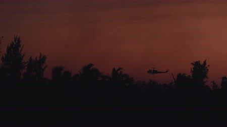 Rescue fire helicopter collects water into the sea and flies toward the extinguish a tropical forest fire on the background of a beautiful dawn sky. Jungle Fire Prevention
