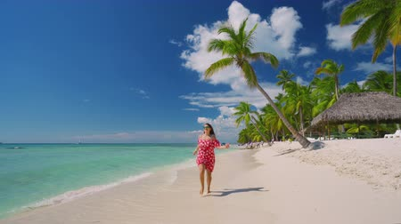 Happy carefree woman enjoying summer vacation in Saona Island and caribbean beaches, Dominican Republic