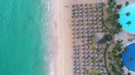 Summer holiday on tropical beach. Aerial top view of sea, lounge chairs, umbrellas and happy people. Punta Cana