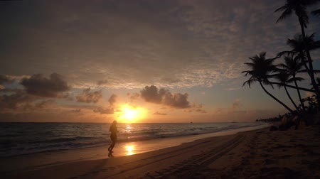 Tropical sunrise with coconut palm trees and exotic paradise island beach. Girl running on sand.