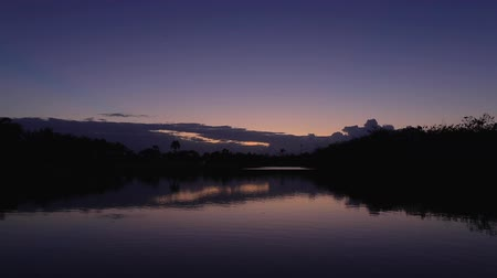Sunset over lake in tropical golf course