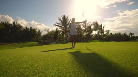 Golf course and champion player near the hole with flag, luxury tropical resort Stok Video
