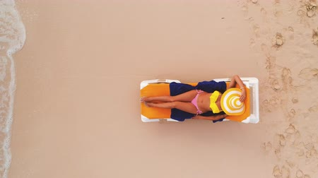 купальник : Beach vacation in paradise tropical island, sexy suntan woman relaxing on beach and sea. Aerial top view.