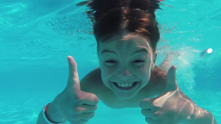 uszoda : Cute teen boy dives in blue pool with open eyes