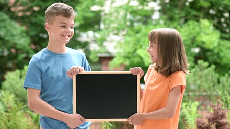 okula geri : Boy and girl with blackboard Stok Video
