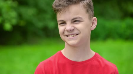 boyish : Happy caucasian teen boy - outdoor in nature portrait. Child in spring or summer city park. Slow motion close-up. Funny cute teenager smiling and looking at camera.
