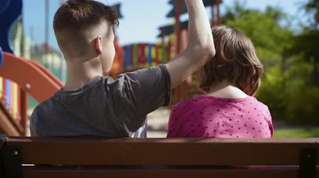 Back view of a couple teenage - teen boy and girl sitting together on the bench outdoors. Friendship and love concept - close-up. Stock Footage