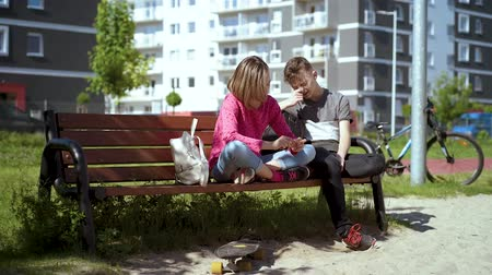 Couple teenage - teen boy and girl sitting together on the bench outdoors. Friendship and love concept - close-up. Stock Footage
