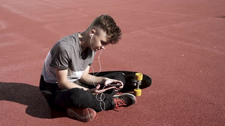Happy teenage boy with headphones are using gadget, smiling while sitting on the playground outdoors. Young student teen with a skateboard playing on tablet pc and listening to music or watches video.