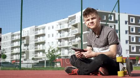 de volta : Happy teenage boy with headphones are using gadget, smiling while sitting on the playground outdoors. Young student teen with a skateboard playing on tablet pc and listening to music or watches video.