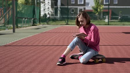Happy teenage girl with headphones are using gadget, smiling while sitting on the playground outdoors. Young student teen with a skateboard playing on tablet pc, listening to music or watches video.