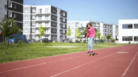 Out of focus - Child skateboarder skateboarding on the playground outdoors. Young student teen girl with a skateboard.
