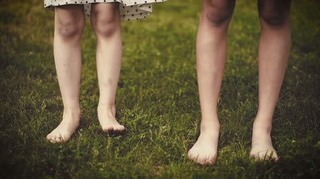 Slow motion shot of bare feet of little girls walking, jumping and running on green grass. Happy children playing outdoors in spring or summer park. Fun at field - retro.