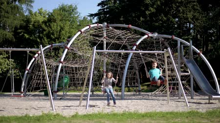 братья и сестры : Happy two children ride on a swing at summer park. Cute teen boy and girl swings at playground outdoors.