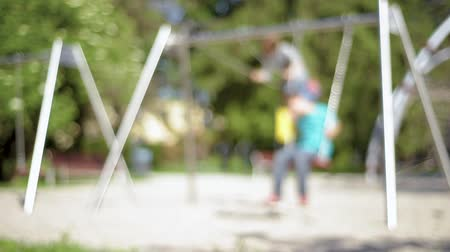 Out focus of two happy children ride on a swing at summer park. Cute teen boy and girl swings at playground outdoors.