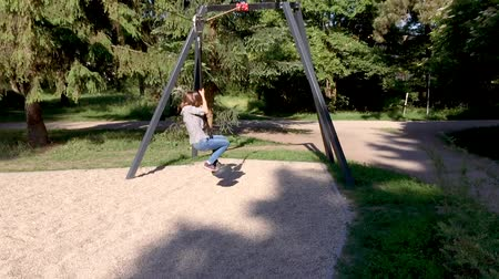 zip line : Children having fun is riding zipline. Cute girl and teen boy moving on zip line at playground - outdoors.