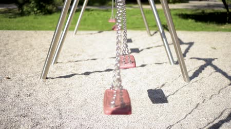 Abandoned empty swings swaying in the wind at children playground outdoors