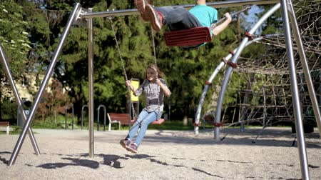 Happy two children ride on a swing at summer park. Cute teen boy and girl swings at playground outdoors.