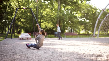 Children having fun is riding zipline. Cute girl and teen boy moving on zip line at playground - outdoors.