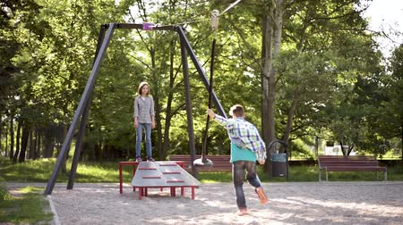 zipline : Children having fun is riding zipline. Cute girl and teen boy moving on zip line at playground - outdoors.