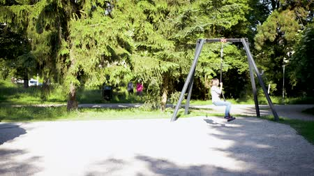 Child having fun is riding zipline. Cute girl moving on zip line at playground - outdoors.