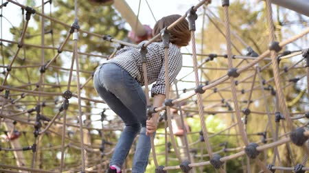 детская площадка : Happy children in adventure park. Cute girl having fun and climbing on a rope at playground outdoors. Стоковые видеозаписи