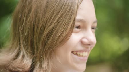 Close up emotional portrait of caucasian smiling teen girl. Funny cute teenager in summer park at day. Child looking away.