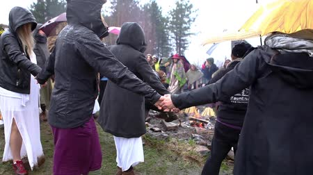 şenlik ateşi : Women holding hands, turning in circles around a rainy day (Package of 4 scenes, fixed angle, close-up on the fire) Stok Video