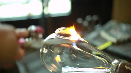 hot rod : Blown Glass - Man making a hole in a big translucent lantern using fire in a factory environment (package of 7 scenes)