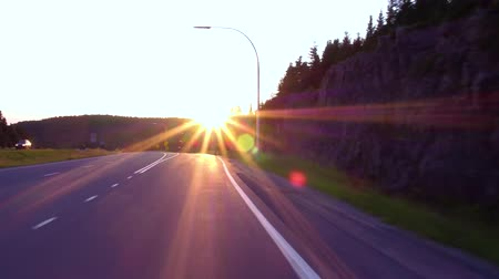 samochody : Exiting on the highway at sunset, with the sun in exiting (driving in northern Quebec, Canada)