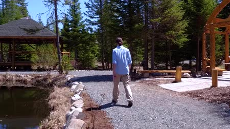 léčit : Man walking on the forest with a blue sky in the background (light slow motion and travellling forward)